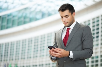 Young businessman using his mobile phone. Copy-space on the left