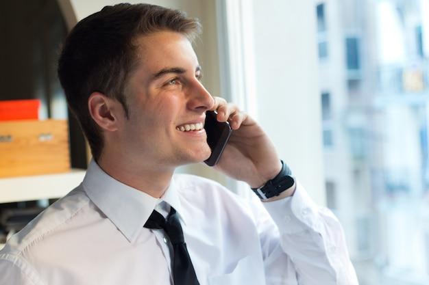 사무실에서 그의 휴대 전화를 사용하는 젊은 사업가.