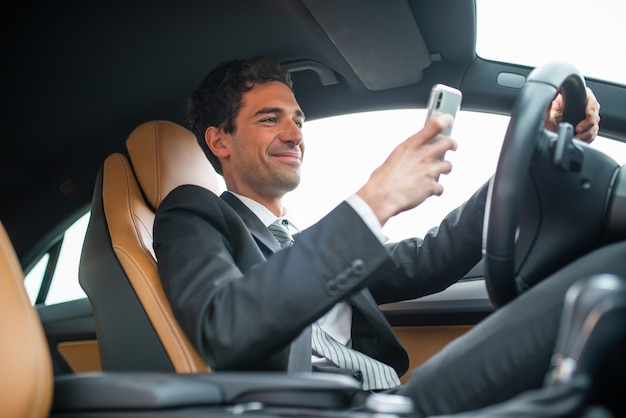 Young businessman using his mobile phone while driving, dangerous behaviour concept