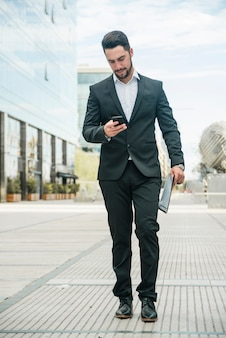 Young businessman using his phone while walking on pavement in the campus