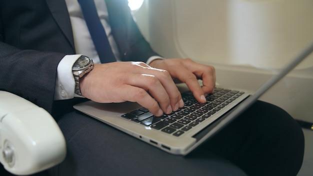 Молодой предприниматель, используя портативный компьютер в самолете. концепция деловой поездки.