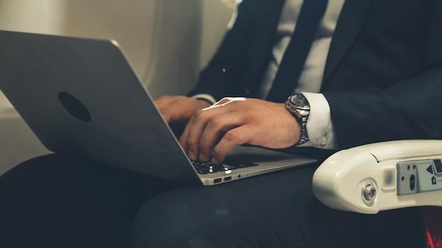 Молодой предприниматель, используя портативный компьютер в самолете. деловая поездка концепция путешествия.