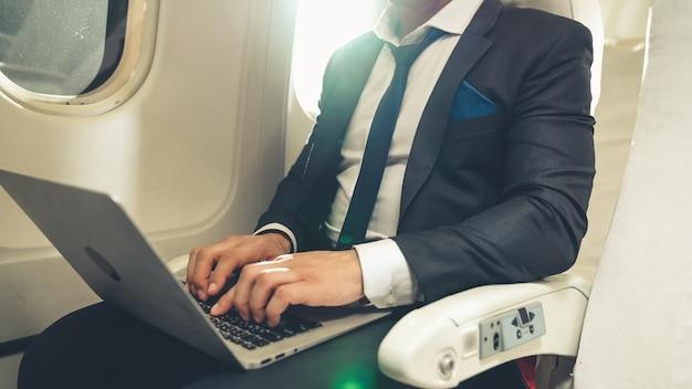 Молодой предприниматель с помощью портативного компьютера в самолете