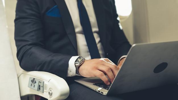 飛行機の中でラップトップコンピューターを使用して青年実業家