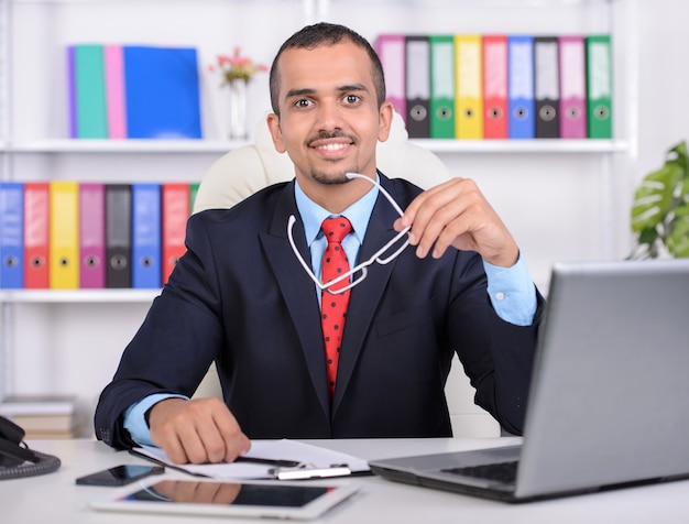 Young businessman, using laptop, sitting in office.