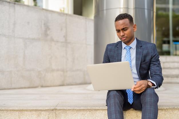 야외 계단에 앉아있는 동안 노트북을 사용하는 젊은 사업가