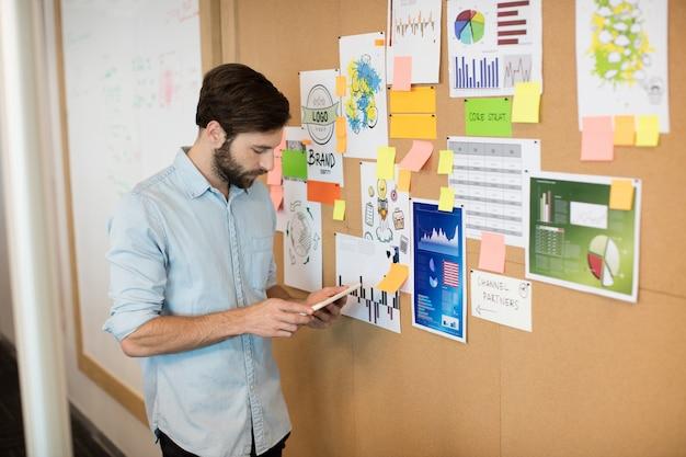 Молодой предприниматель с помощью мобильного телефона на мягкой доске