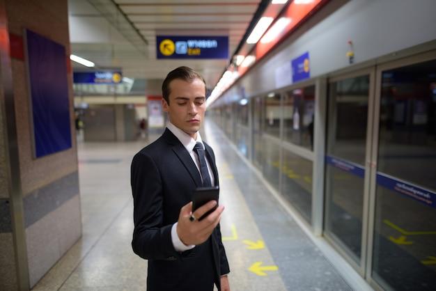 Молодой предприниматель с помощью телефона на вокзале