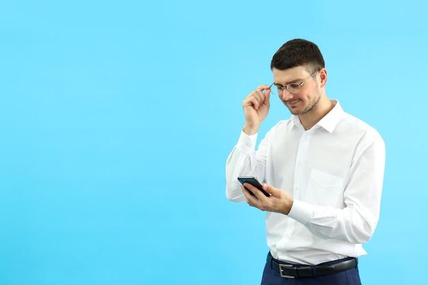 Молодой бизнесмен с помощью телефона на синем фоне.