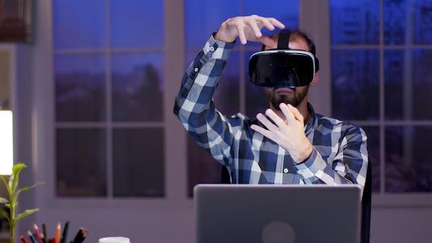 Молодой бизнесмен, используя очки виртуальной реальности, работая в домашнем офисе в ночное время.