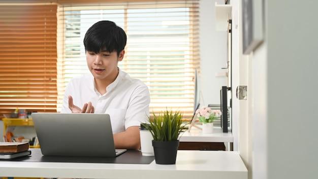 젊은 사업가가 집에서 일하는 동안 동료들과 화상 회의를 합니다.