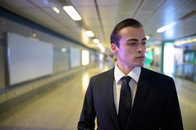 Молодой бизнесмен гуляет и думает на вокзале