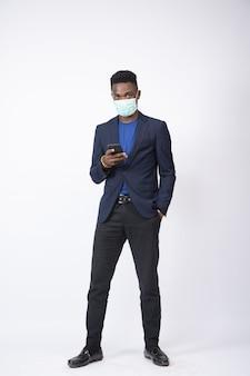 흰 벽 앞에서 전화기를 사용하여 양복과 얼굴 마스크를 쓴 젊은 사업가