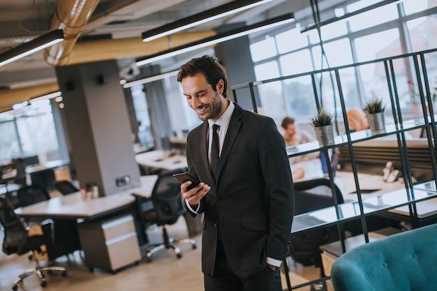 オフィスで現代のスマートフォンを使用して黒のスーツを着ている青年実業家
