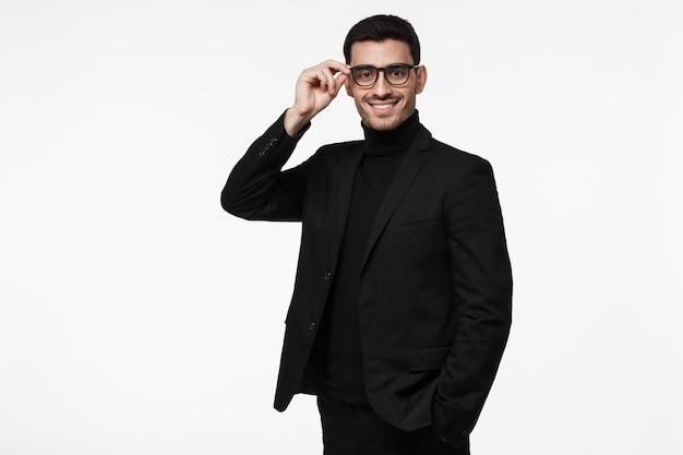 Молодой бизнесмен в черном костюме с водолазкой и очками