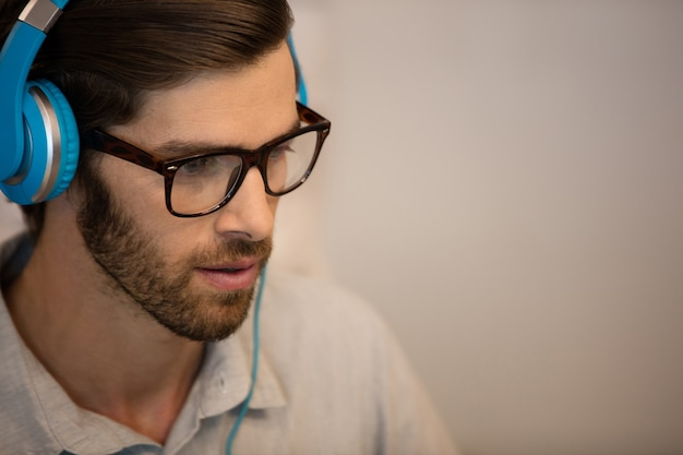 블루 헤드폰을 착용하는 젊은 사업가