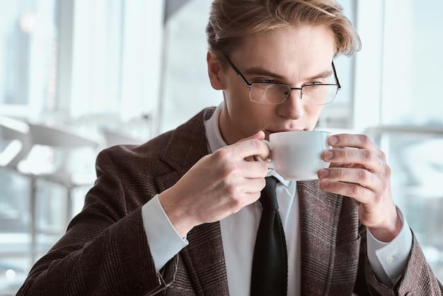 사무실에서 안경을 쓴 젊은 사업가가 뜨거운 에스프레소 커피를 마시는 컵을 들고 테이블에 앉아 사려깊은 클로즈업
