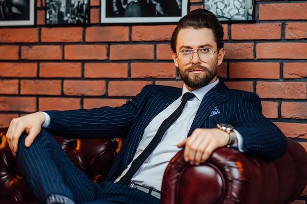 Молодой бизнесмен в модных очках и стильном костюме, сидя на софе.
