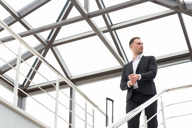 Young businessman wearing formal suit standing on a stairs in modern building with suitcase