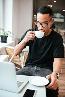 Young businessman wearing glasses sitting near window and typing by laptop computer while drinking coffee