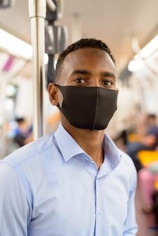 コロナウイルスの発生から保護するためにマスクを着用し、電車の中で距離を置いて立っている青年実業家