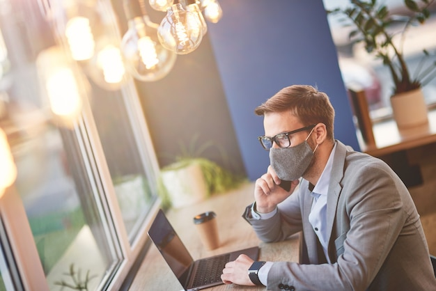 노트북을 사용하여 보호용 안면 마스크를 쓰고 파트너와 전화 통화를 하는 동안 젊은 사업가