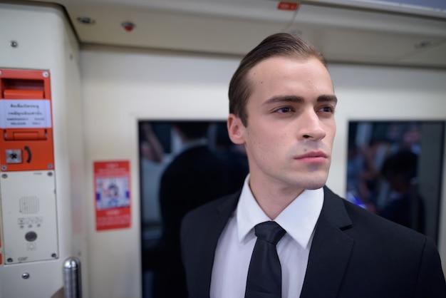 Молодой бизнесмен в костюме и мышление внутри поезда