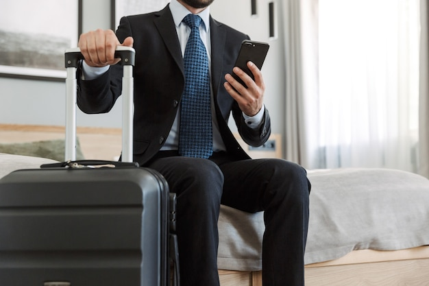 Молодой бизнесмен в костюме сидит в гостиничном номере, используя мобильный телефон, неся чемодан