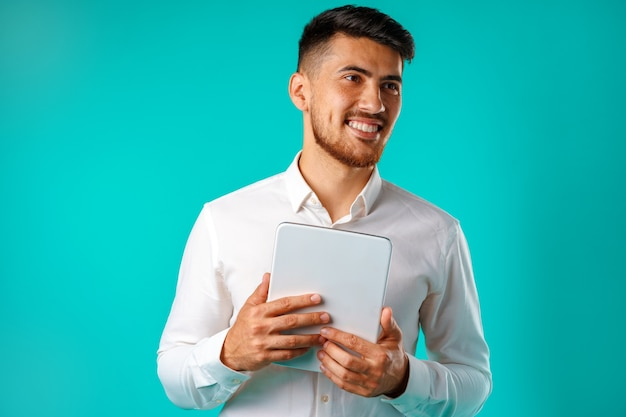 Young businessman wearing white shirt holds digital tablet isolated