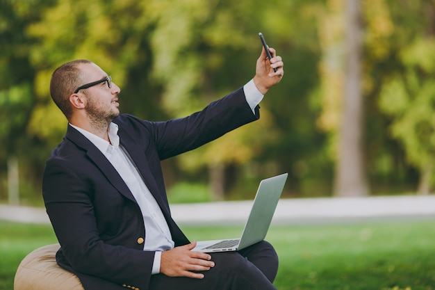 Young businessman in white shirt, classic suit, glasses. man sit on soft pouf with laptop pc computer, doing selfie on mobile phone in city park on green lawn outdoors. mobile office business concept.