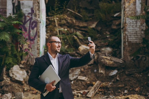 Young businessman in white shirt, classic suit, glasses. man standing with laptop pc computer, doing selfie on mobile phone near ruins debris, stone building outdoors. mobile office, business concept.
