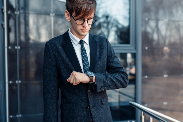 A young businessman who is late for work looks at the clock on his hand