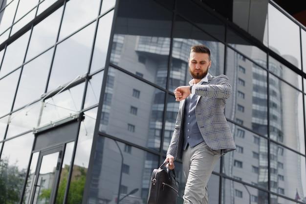 モダンなオフィスビルを背景に街の通りを走るブリーフケースを持つ青年実業家