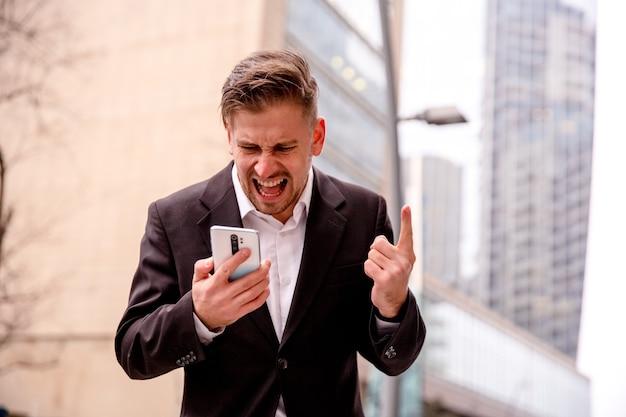 Молодой бизнесмен с чашкой кофе в руках говорит по телефону, кричит