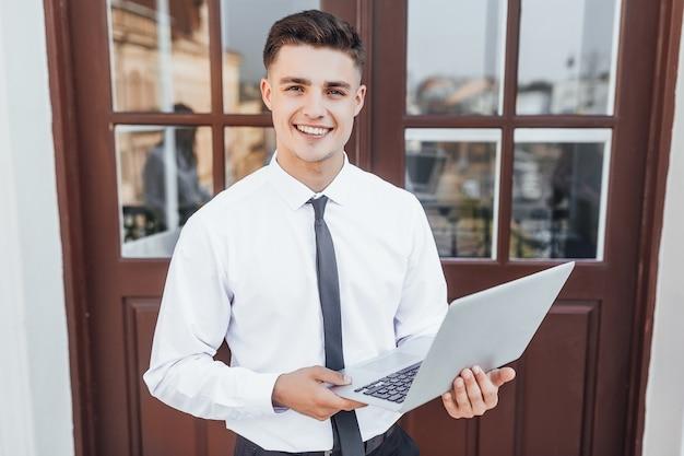 Молодой бизнесмен с ноутбуком в руках