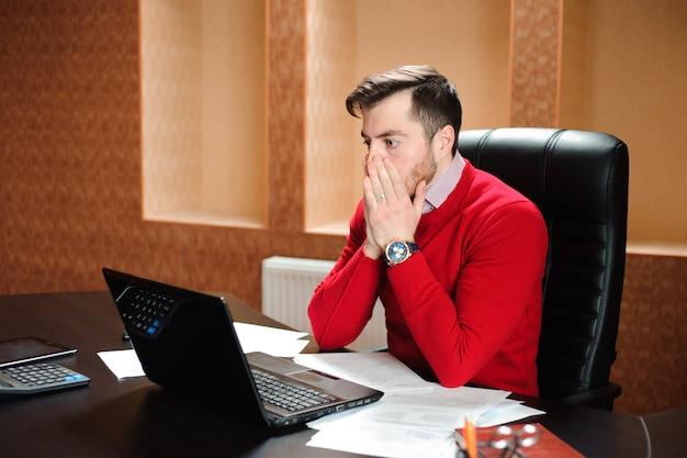 Молодой бизнесмен с проблемой на офисе сидя на его столе хмуриться на его экране компьютера.