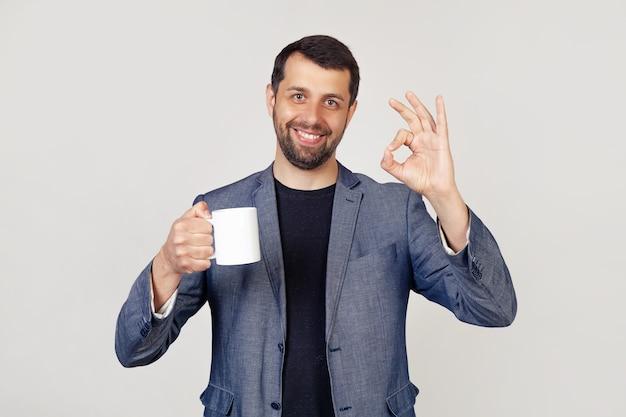 Молодой бизнесмен с улыбкой, мужчина с бородой в куртке, держащий чашку кофе и показывающий жестом, все в порядке, мужчина со счастливым лицом.