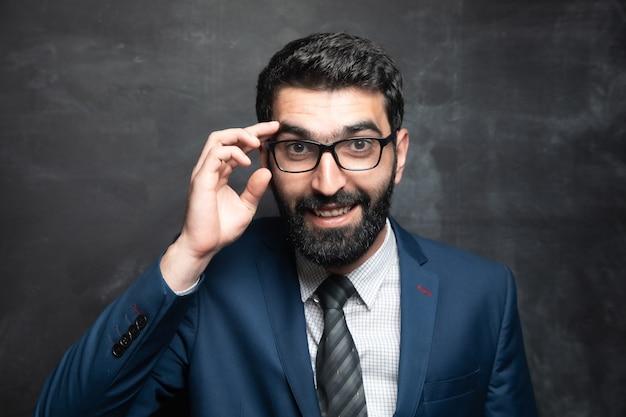 Молодой бизнесмен с улыбкой держит очки на темной поверхности