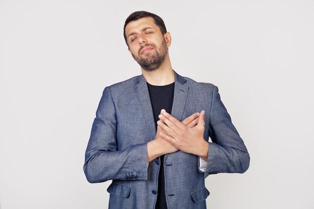 Молодой бизнесмен с улыбкой мужчина с бородой в куртке, улыбаясь, положив руки на грудь, с закрытыми глазами и с благодарным жестом на лице. концепция здоровья.