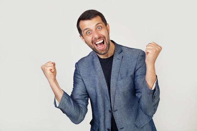 ジャケットにひげを生やした笑顔の男性を持つ青年実業家は、非常に幸せで興奮しており、挙手で勝者のジェスチャーをし、笑顔で成功について叫んでいます。お祝いのコンセプト。