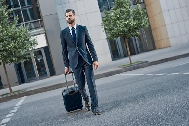 바퀴에 여행 가방을 든 젊은 사업가가 텅 빈 길을 걷는다