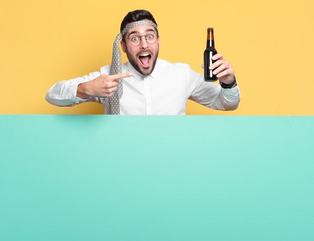 Young businessman with a beer bottle celebrating good news