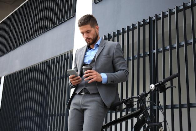 街の通りで自転車とスマートフォンを持つ青年実業家。