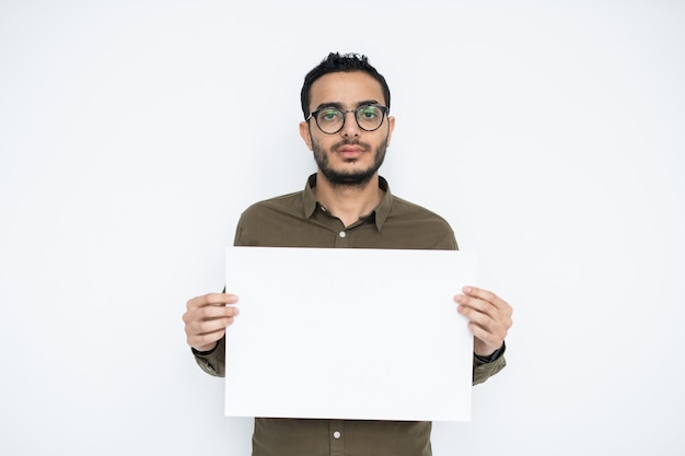 Young businessman with blank face holding empty poster in isolation