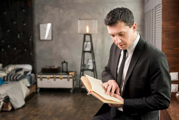 Young businessman with book relaxing at home