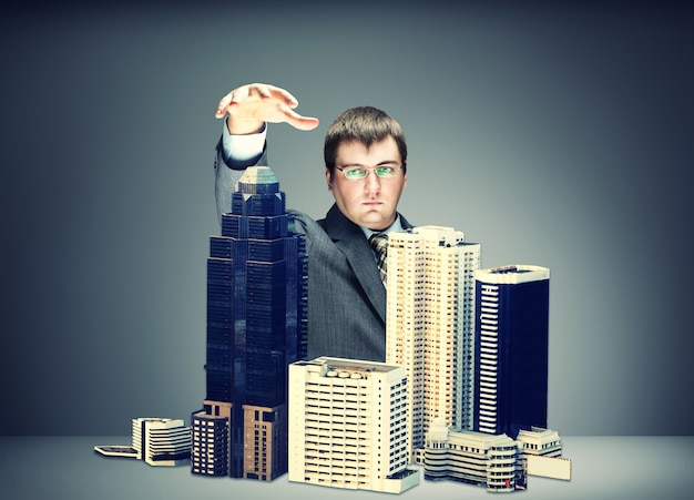 Young businessman with buildings isolated on gray