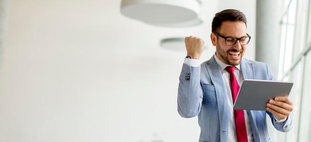 Молодой бизнесмен с цифровой планшет в офисе