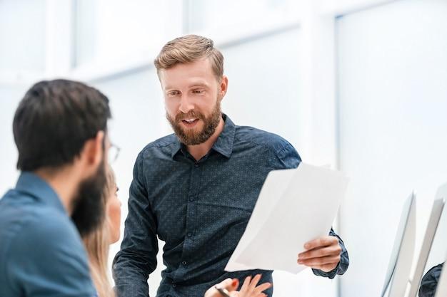 Молодой бизнесмен с документами, что-то объясняя своим коллегам
