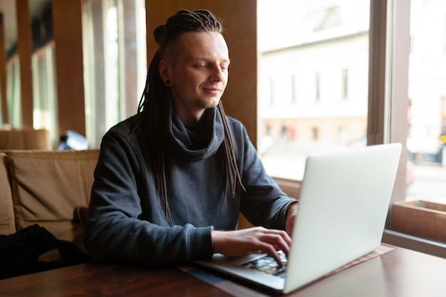 Young businessman with dreadlock having doing his work in cafe with laptop.