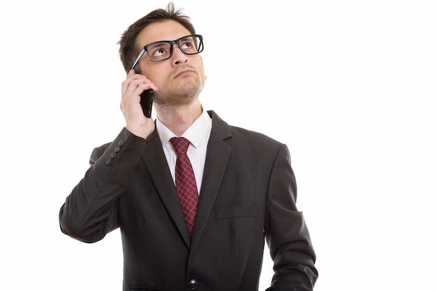 携帯電話で話している眼鏡を持つ青年実業家